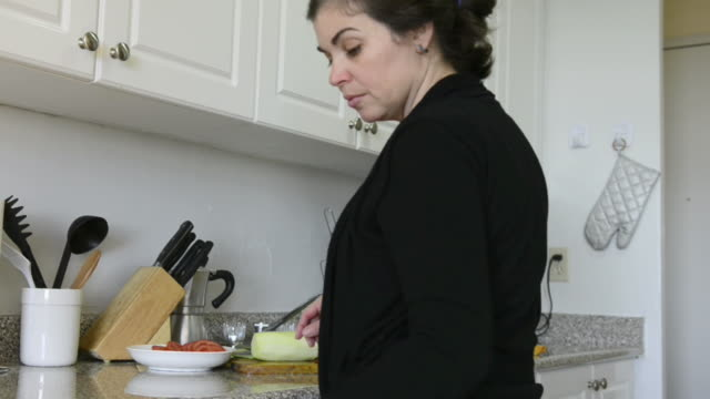 hispanic housewife real-life woman prepares salad and vegetables in her apartment building's kitchen. - 黒のシャツ点の映像素材/bロール