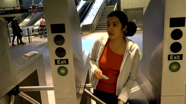 Hispanic Latin American woman commuter successfully swipes a subway MetroCard through a turnstile at the 34th Street Hudson Yards Subway Station...