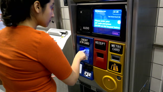 Hispanic Latin American woman in her early 30's buying a subway MetroCard via a vending machine kiosk at the 34th Street Hudson Yards Subway Platform...