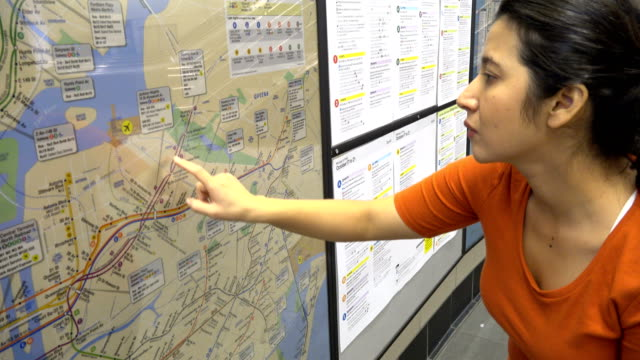Hispanic Latin American woman looking at a paper poster subway metro map of New York City mounted on a wall / Hudson Yards Subway Station Train...