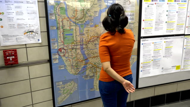 stockvideo's en b-roll-footage met hispanic latin american woman looking at a paper poster subway metro map of new york city mounted on a wall / hudson yards subway station train... - mid volwassen vrouw
