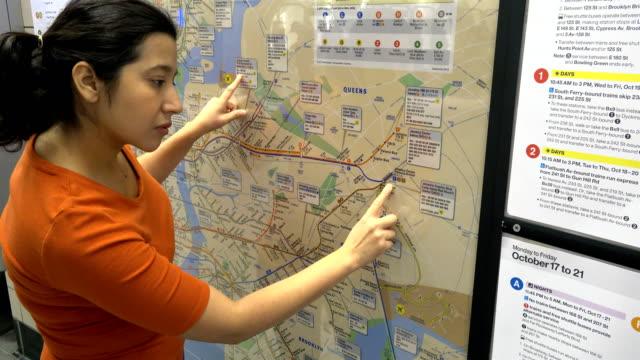 vídeos de stock e filmes b-roll de hispanic latin american woman looking at a paper poster subway metro map of new york city mounted on a wall / hudson yards subway station train... - só mulheres de idade mediana