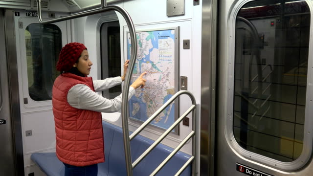 hispanic latin american woman looking at a paper subway metro map of new york city inside the number seven train / hudson yards subway platform train... - number 7 stock videos & royalty-free footage