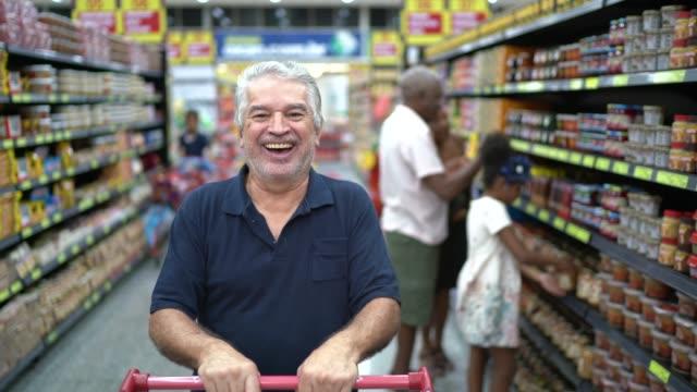 vídeos de stock, filmes e b-roll de retrato de homem sênior latino hispânico no supermercado - rotina