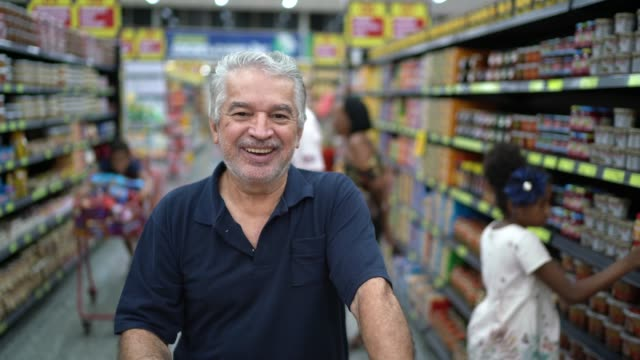 hispanic latino senior man portrait at supermarket - modern manhood stock videos & royalty-free footage