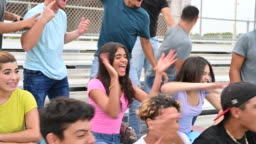 Hispanic male and female teenagers cheering from bleachers
