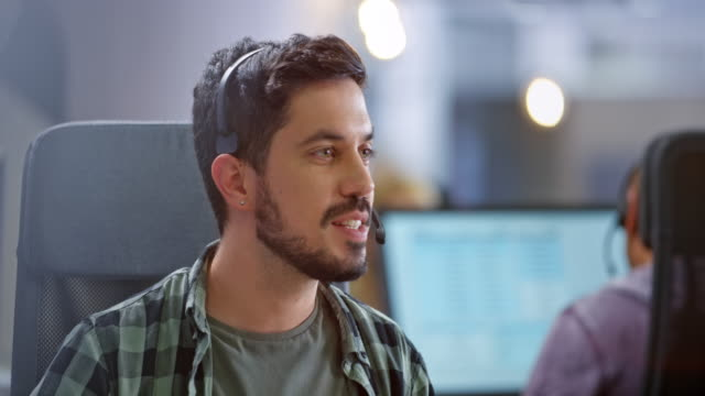 hispanic male call center agent smiling while providing customer support - call center stock videos & royalty-free footage