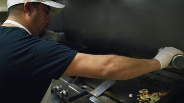 hispanic male cook in his thirties sprinkles seasoning before stirring vegetables on a griddle at a mexican restaurant - glove video stock e b–roll