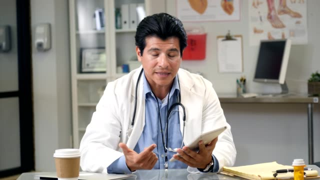 hispanic male doctor video conferences with patient - instructions stock videos & royalty-free footage