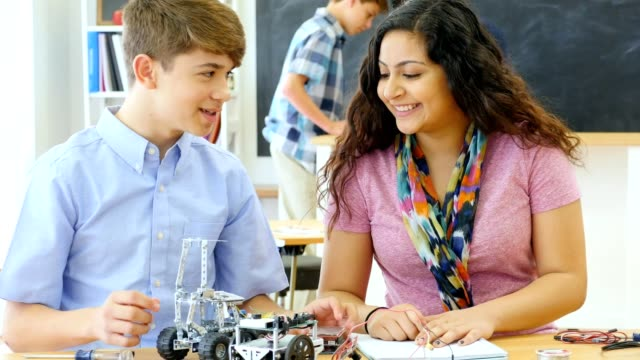 Hispanic male high school student teaches classmate how to build robotic vehicle