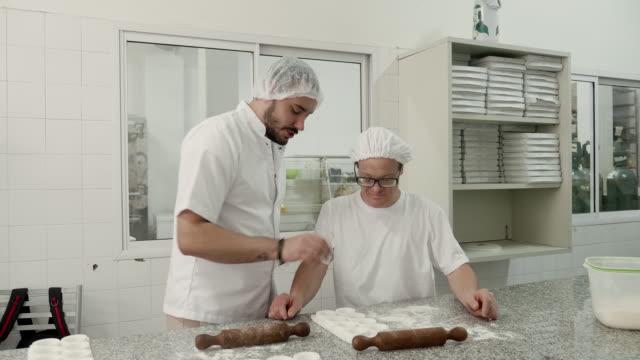 hispanic male supervisor guiding coworker in pasta factory - haarnetz stock-videos und b-roll-filmmaterial