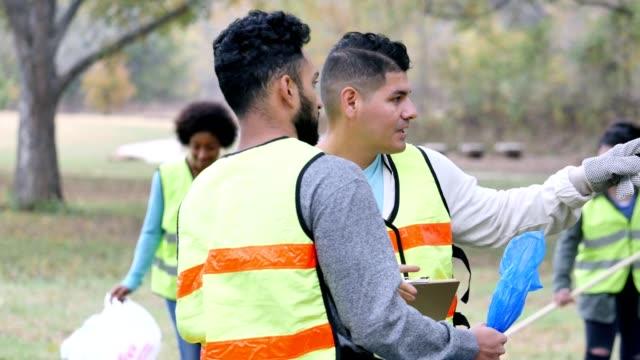 Hispanic male volunteer coordinator instructs volunteer on park cleanup