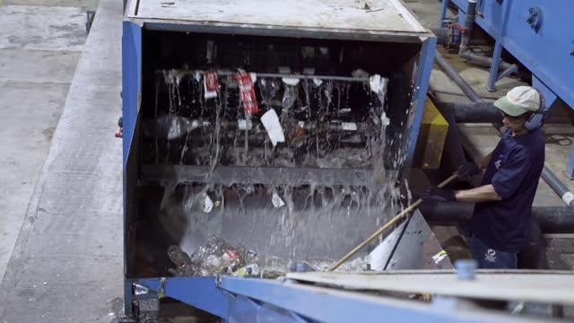 プラスチック工場のリサイクルpet洗浄プロセスにおけるヒスパニック系男性労働者 - リサイクル工場点の映像素材/bロール