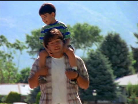 vídeos de stock e filmes b-roll de hispanic man carrying young boy on shoulders walking toward camera outdoors - carregar uma pessoa nos ombros