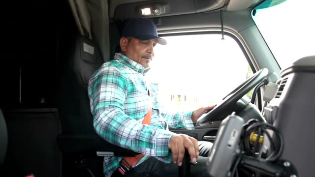 Hispanic man climbing into cab of semi-truck