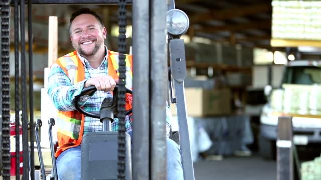 vídeos de stock e filmes b-roll de hispanic man climbs onto forklift in lumberyard - aproximar