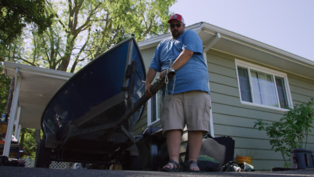 a hispanic man in his forties attaches a small boat on a trailer to a vehicle's hitch for towing outside his home on a sunny day - chain stock videos & royalty-free footage