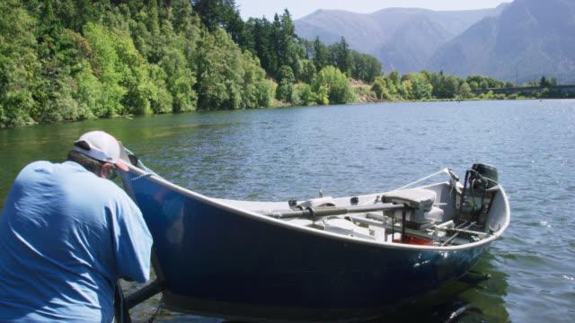 stockvideo's en b-roll-footage met een spaanse mens in zijn jaren '40 ontkoppelt zijn kleine boot van zijn aanhangwagen naast een helling van de boot in de rivier van colombia in washington op een zonnige dag - aanhangwagen