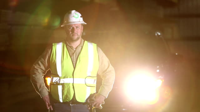 hispanic man in reflective vest and hardhat at night - reflective clothing stock videos & royalty-free footage