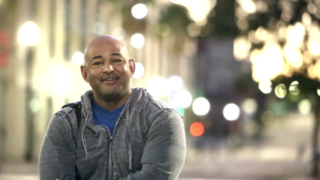 vídeos de stock e filmes b-roll de hispanic man in the city at night, takes off hat - sweatshirt