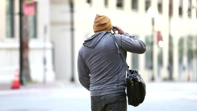 vidéos et rushes de homme hispanique dans la ville parlant sur le téléphone intelligent - être perdu