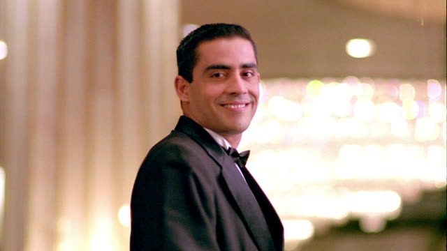 MS PORTRAIT Hispanic man in tuxedo (waiter) turning toward camera smiling indoors