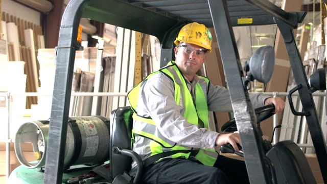 hispanic man in warehouse climbs onto forklift - forklift stock videos & royalty-free footage