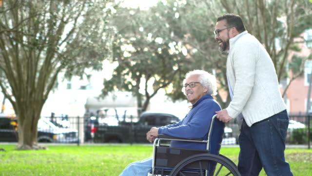 hispanic man pushing senior father in wheelchair - pushing stock videos & royalty-free footage