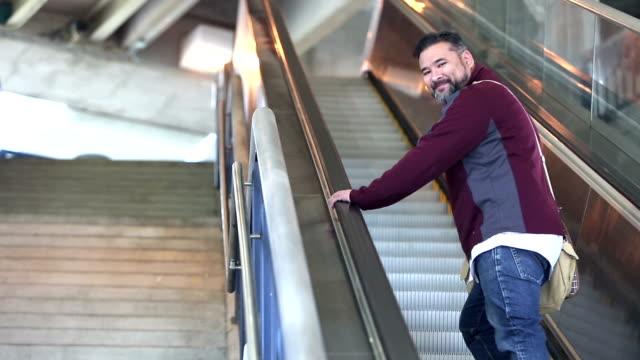 hispanic man riding up escalator - shoulder bag stock videos & royalty-free footage