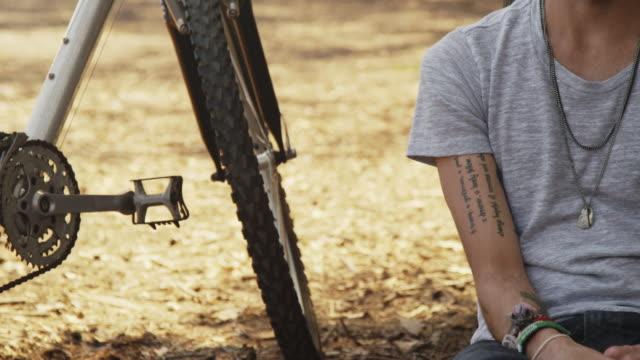 hispanic man sitting by bike outdoors - プエルトリコ人点の映像素材/bロール