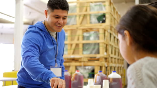 Hispanic man volunteering in food bank, serving meals to children in line