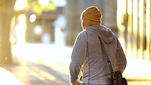 vidéos et rushes de homme hispanique marchant dans la ville, regardant autour - partir
