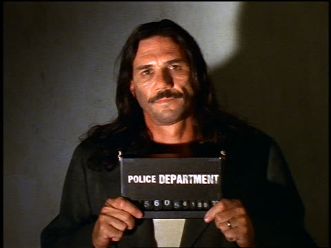 portrait hispanic man with mustache + long hair holding sign + having mug shot taken at police station - mug shot stock videos & royalty-free footage