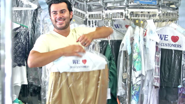 hispanic man working at dry cleaners - launderette stock videos & royalty-free footage