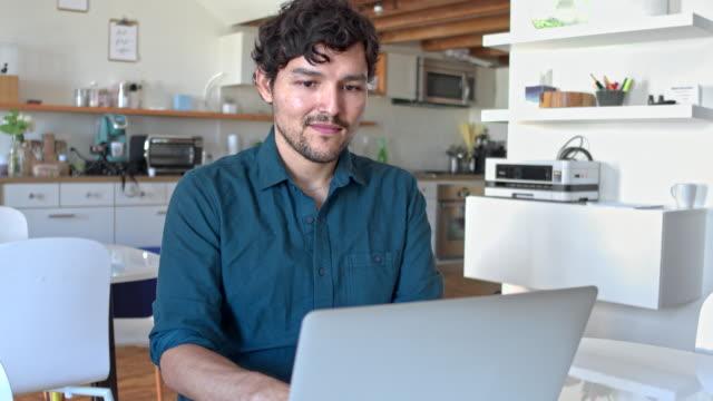 vídeos de stock, filmes e b-roll de homem hispânico, trabalhando com o laptop em casa - negócios finanças e indústria
