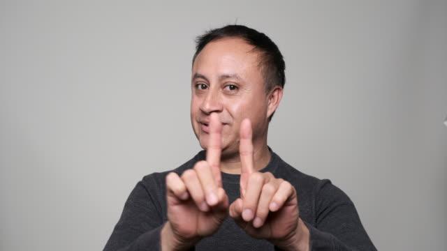 ヒスパニックの成熟した男は、彼の人差し指でジェスチャーをしないと言う - 断る点の映像素材/bロール