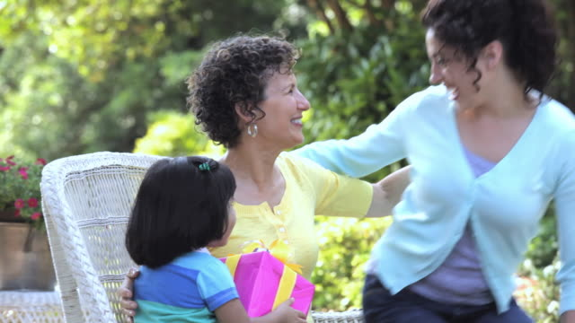 hispanic mother and daughter greeting grandmother with present, richmond, virginia, united states - mother's day stock videos & royalty-free footage