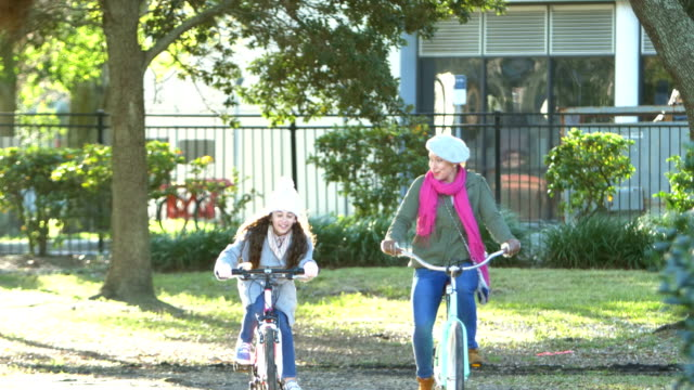 hispanic mother and daughter riding bikes in park - winter coat stock videos & royalty-free footage