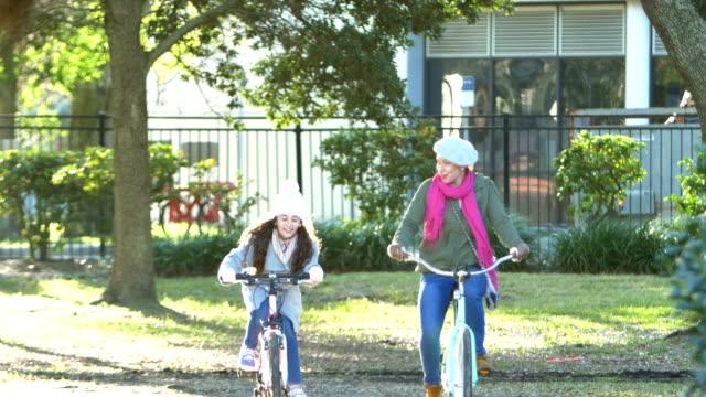 madre e figlia ispaniche in bici nel parco - cappotto invernale video stock e b–roll