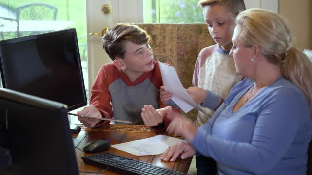 stockvideo's en b-roll-footage met spaanse moeder en zonen die, thuis bestuderen studeren - 45 49 jaar