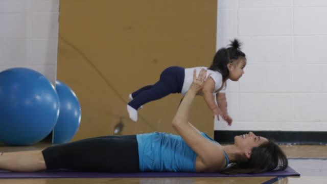 Hispanische Mutter Training mit ihrem Babymädchen