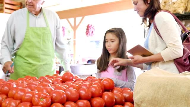 vídeos de stock, filmes e b-roll de hispânica mãe ensinando sua jovem filha é a escolher tomates no mercado de produtos - feirante