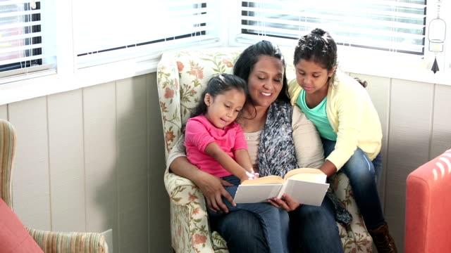 vídeos de stock, filmes e b-roll de matriz latino-americano que lê a suas duas meninas - perguntando