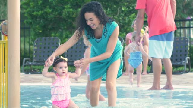 vídeos y material grabado en eventos de stock de madre hispana, niño caminando en la piscina de los niños - encuadre de tres cuartos