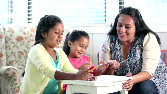 hispanic mother with daughters doing homework - family with two children stock videos & royalty-free footage