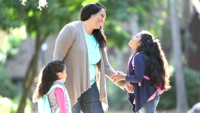 hispanic mother with schoolgirls, older one talking - first day of school stock videos & royalty-free footage