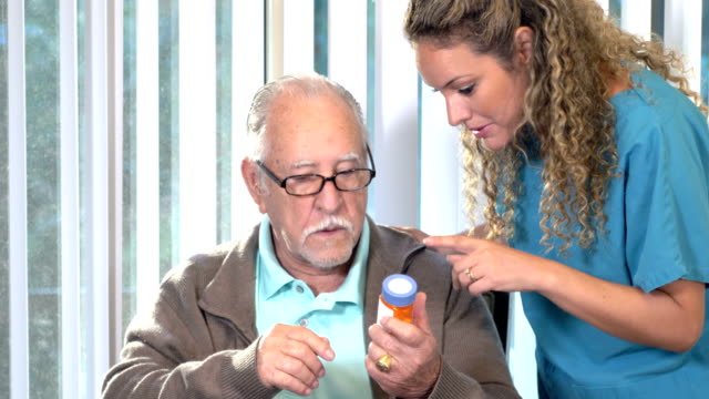 hispanic nurse explaining medication to senior man - prescription medicine home stock videos & royalty-free footage