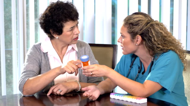 hispanic nurse explaining medication to senior woman - female nurse stock videos & royalty-free footage