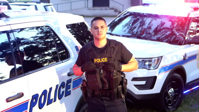 hispanic officer standing by police cars - ufficiale grado delle forze armate video stock e b–roll