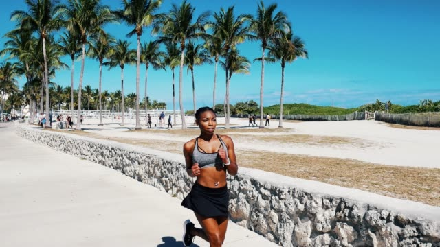 hispanic or afro caribbean woman jogging in the morning near the beach in usa - palm tree stock videos & royalty-free footage